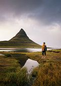 Young hiker with a backpack looks at the Kirkjufell mountain in Iceland. This 463 m high mountain is located on the north coast of Icelands Snaefellsnes peninsula. poster