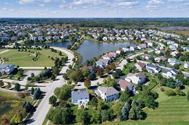 Aerial view of a residential community with pond in a suburban location.