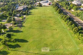 Aerial view of a soccer game in progress in a suburban setting.