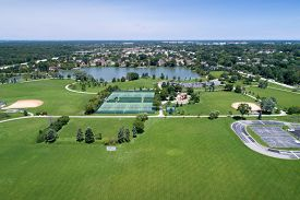 Aerial view of a large playfield in a suburban area with ballfields, tennis courts, and a lake.