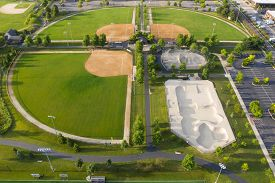 Aerial view of a suburban baseball/softball sports complex with batting cages and a skate park.