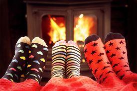 Feet in wool socks near fireplace in winter