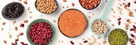 Legumes Variety Panoramic Top-down Shot On A White Background. Vibrant Pulses Including Colorful Bea