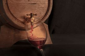 Pouring Wine Into A Glass From A Barrel, A Closeup On A Dark Background With Copy Space, Toned Image
