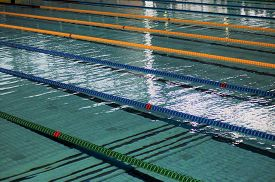 Indoor Swimming Pool. Ropes Divide The Swimming Lanes Of An Indoor Pool Ahead Of A Swim Meet Inside