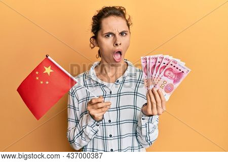 Young brunette woman holding china flag and yuan banknotes in shock face, looking skeptical and sarcastic, surprised with open mouth