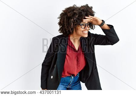 African american woman with afro hair wearing business jacket and glasses very happy and smiling looking far away with hand over head. searching concept.