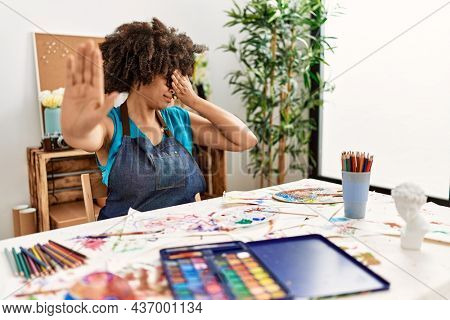 Beautiful african american woman with afro hair painting at art studio covering eyes with hands and doing stop gesture with sad and fear expression. embarrassed and negative concept.