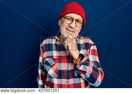 Handsome mature man wearing hipster look with wool cap looking confident at the camera with smile with crossed arms and hand raised on chin. thinking positive.