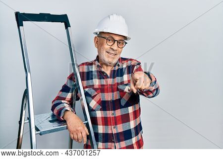 Handsome mature handyman close to construction stairs wearing hardhat pointing to you and the camera with fingers, smiling positive and cheerful