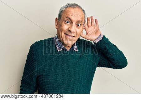 Handsome senior man with grey hair wearing casual sweater smiling with hand over ear listening and hearing to rumor or gossip. deafness concept.