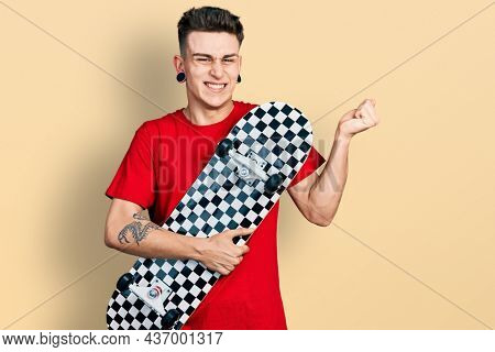 Young caucasian boy with ears dilation holding skate screaming proud, celebrating victory and success very excited with raised arm