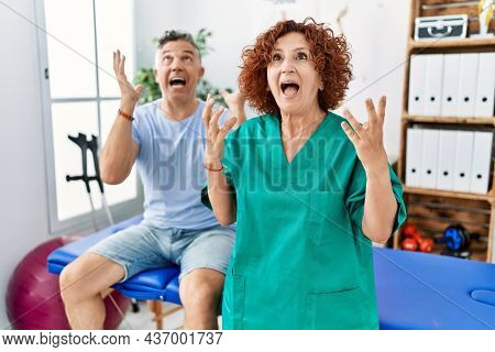 Physiotherapy woman working at pain recovery clinic with patient crazy and mad shouting and yelling with aggressive expression and arms raised. frustration concept.