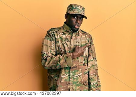 Young african american man wearing army uniform pointing aside worried and nervous with forefinger, concerned and surprised expression