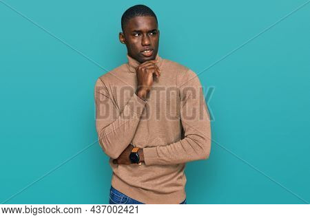 Young african american man wearing casual winter sweater with hand on chin thinking about question, pensive expression. smiling with thoughtful face. doubt concept.