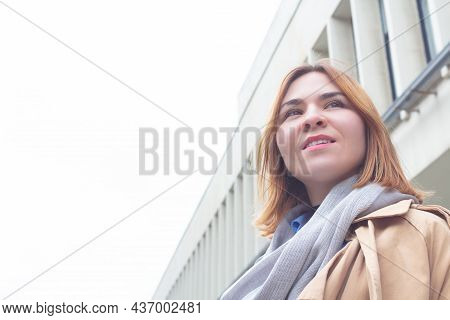 Beautiful Young Caucasian Business Woman In Trench Standing Near Office Building, Looking Into The D