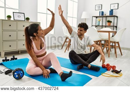 Young latin couple smiling happy training at home. Sitting on the floor high five.