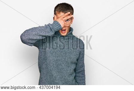 Young blond man wearing casual clothes peeking in shock covering face and eyes with hand, looking through fingers with embarrassed expression.