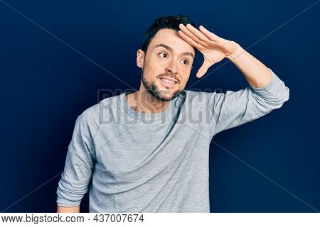 Young hispanic man wearing casual clothes very happy and smiling looking far away with hand over head. searching concept.