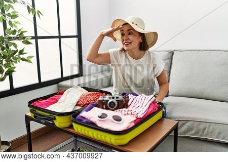 Beautiful middle age hispanic woman packing summer clothes in suitcase very happy and smiling looking far away with hand over head. searching concept.