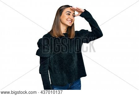Beautiful brunette woman wearing elegant sweater very happy and smiling looking far away with hand over head. searching concept.