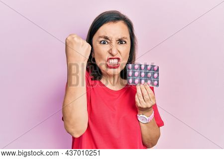 Middle age hispanic woman holding pills annoyed and frustrated shouting with anger, yelling crazy with anger and hand raised