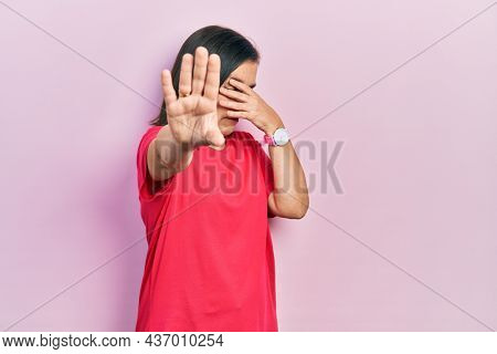 Middle age hispanic woman wearing casual clothes covering eyes with hands and doing stop gesture with sad and fear expression. embarrassed and negative concept.
