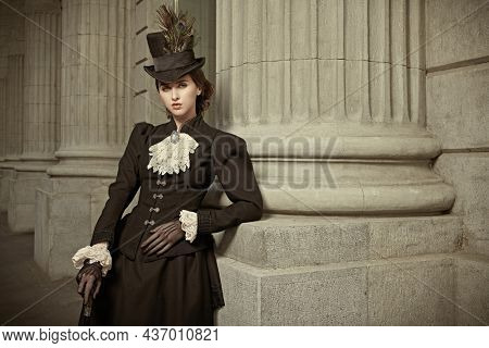 Portrait of an elegant 19th century lady posing on a city street. History and Fashion of the late 19th - early 20th century.