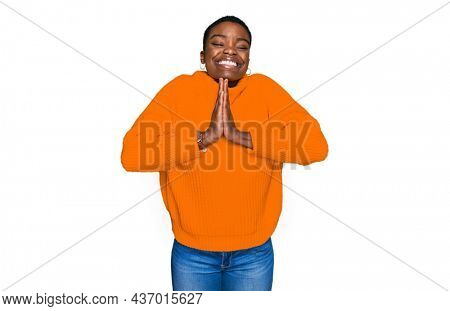Young african american woman wearing casual clothes praying with hands together asking for forgiveness smiling confident.
