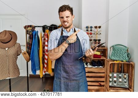 Handsome young man working as manager at retail boutique pointing aside worried and nervous with forefinger, concerned and surprised expression