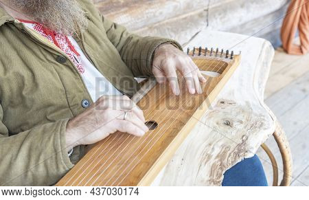 A Man In Ethnic Clothes Plays An Ancient Musical Instrument. A Bearded Man, A Forester Has Built A H