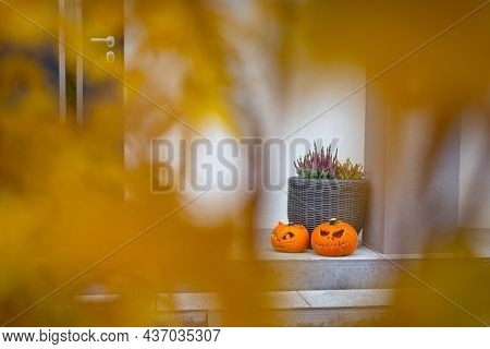 Scary Halloween pumpkins as decoration on the front steps
