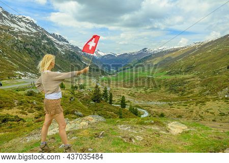 Woman With Swiss Flag On The Panoramic Road Of The Fluela Pass. High Mountain Pass Of The Swiss Alps
