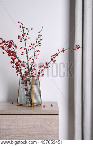 Hawthorn Branches With Red Berries In Vase On Wooden Table Indoors