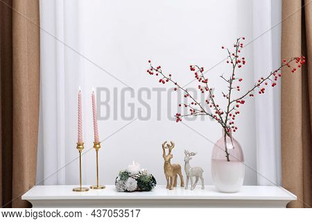 Hawthorn Branches With Red Berries In Vase, Candles And Deer Figures On White Table Near Window Indo