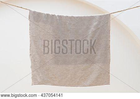 Plain beige towel hanging on a laundry rope