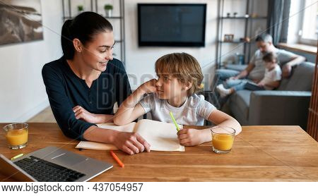 Caring Happy Mother Help Little Teen Son With Homework Study Online On Computer At Home. Smiling Mom