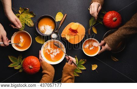 Flat-lay Of Family Or Friends Enjoying Dinner With Pumpkin Cream Soup In Plates On Black Background