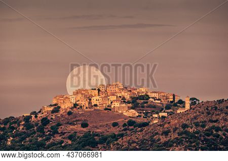 The Full Moon Setting Behind The Hilltop Village Of Sant'antonino In The Balgne Region Of Corsica