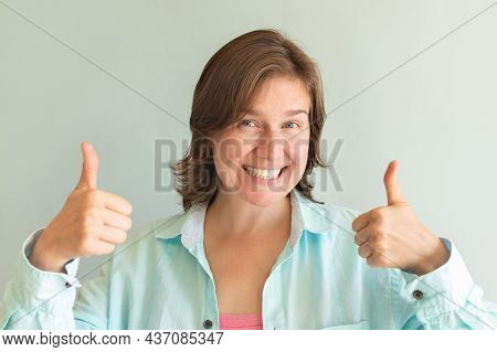 Portrait Of A Funny Emotional Girl On A Blue Background. Emotional Happiness.
