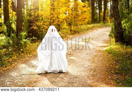 A Child In Sheets With Slits Like A Ghost Costume In An Autumn Forest Scares And Terrifies. A Kind L