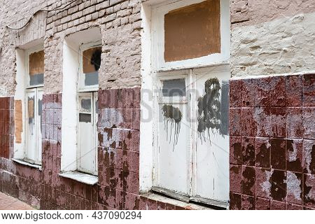 Facade Of Old Shabby Brick House Tiled With Soiled Tiles With Poorly Painted Over White Paint Window