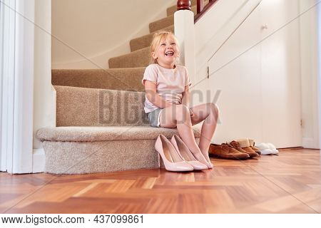Young Girl Sitting On Stairs Dressing Up And Putting On Mother's Shoes