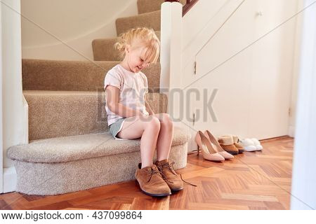 Young Girl Sitting On Stairs Dressing Up And Putting On Parent's Shoes
