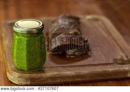 Grilled Steak On A Cutting Board. Piece Of Filet Mignon Cut On A Cutting Board. Jar With Fresh Pesto