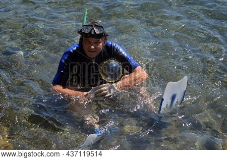 Man in wet suit for underwater activities with dome of action camera for half-underwater photo and video.Marmaris, Turkey