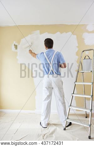 Rear View Of Man Wearing Overalls Painting Wall In Room Of House With Paint Roller