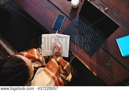 High Angle View Of A Woman Writing In Notebook While Sitting On A Wooden Bench In Front Of A Laptop