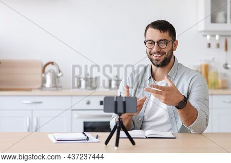 Cheerful Adult European Male Teacher With Beard In Glasses Gesturing And Look At Phone Webcam