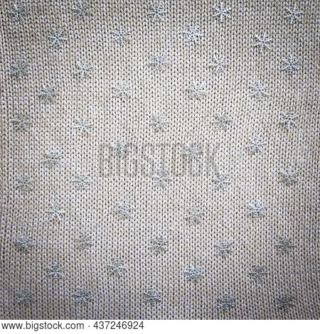 Knitted Background With Snowflakes. Knitted Fabric With Sequins With Snowflakes. Gray Background.